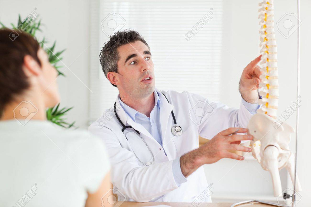 Doctor showing a woman a part of a spine in a room Stock Photo - 11213424