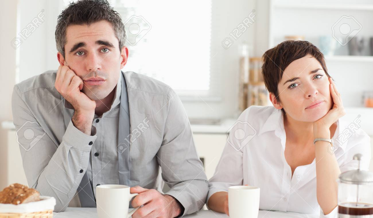 Worn out couple drinking coffee in a kitchen Stock Photo - 11214243