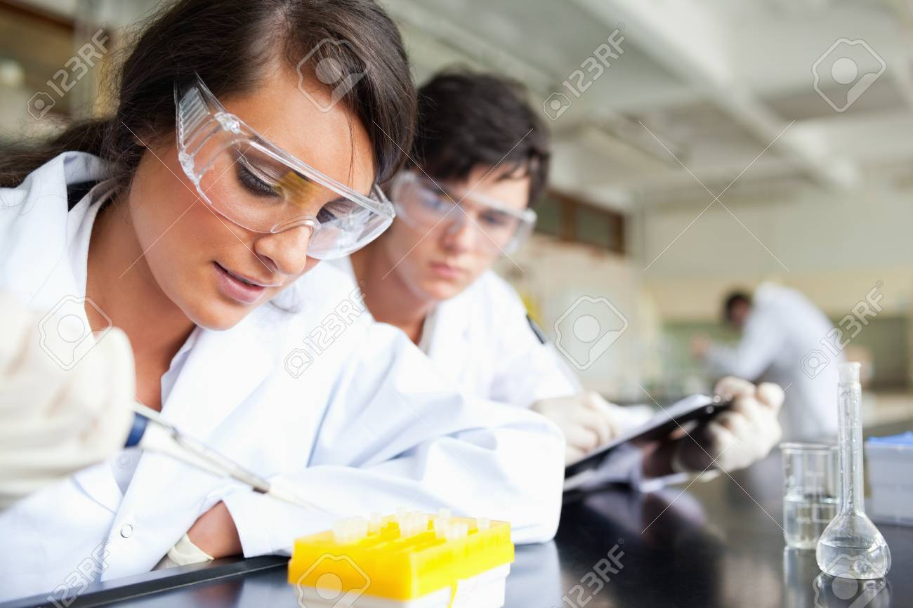 Two young scientists making an experiment in a laboratory Stock Photo - 11187521
