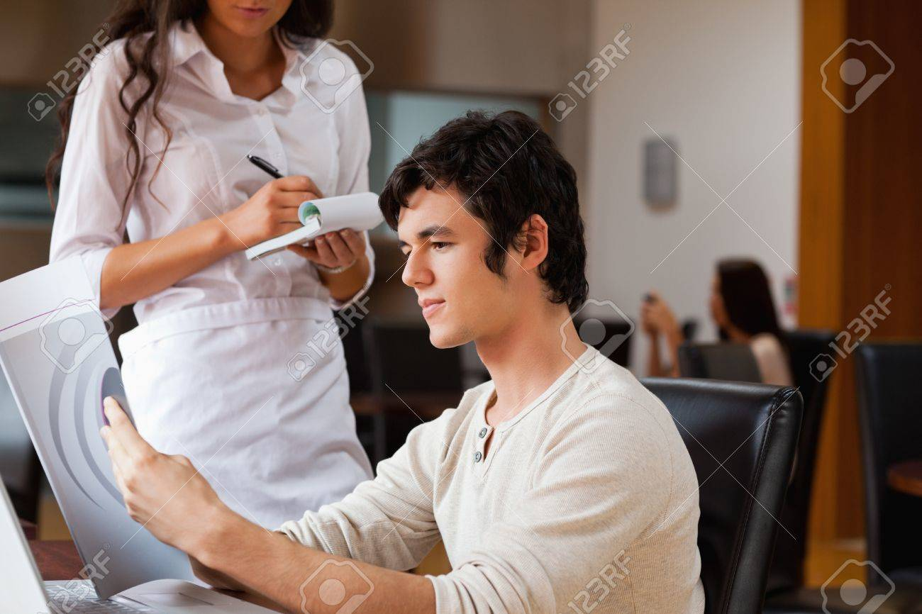 Handsome man ordering food to a waitress in a cafe Stock Photo - 11186515