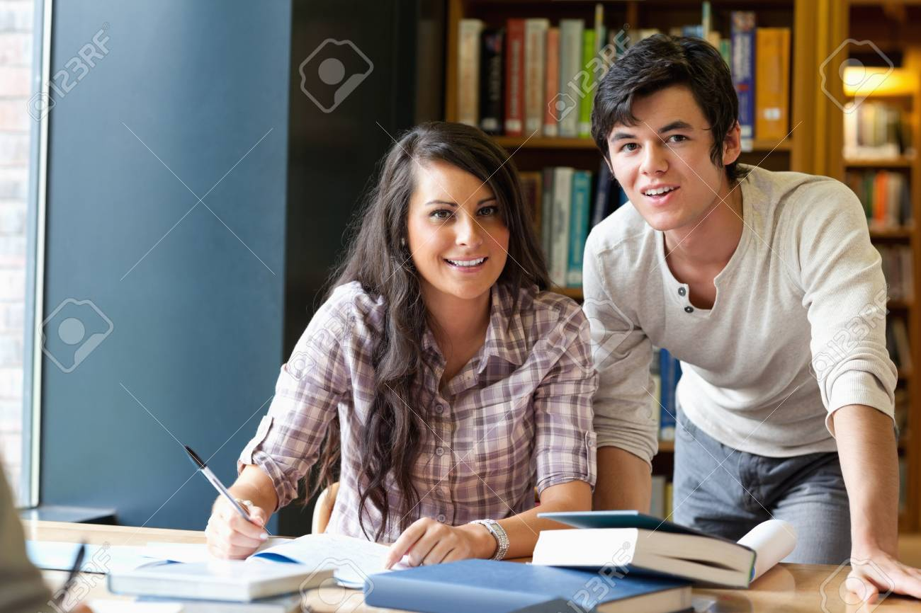 Good looking students posing in a library Stock Photo - 11184755