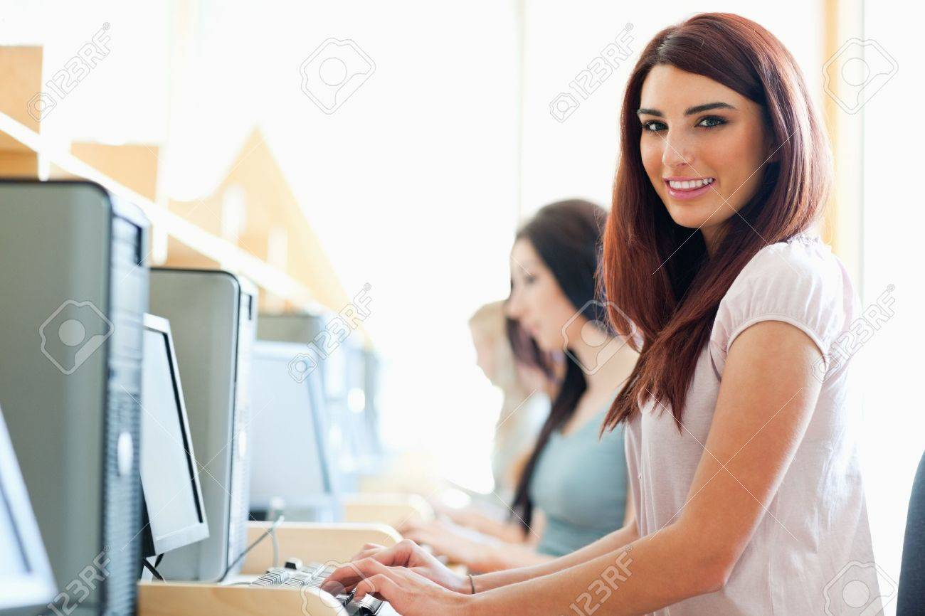 Smiling student using a computer in an IT room Stock Photo - 11190452