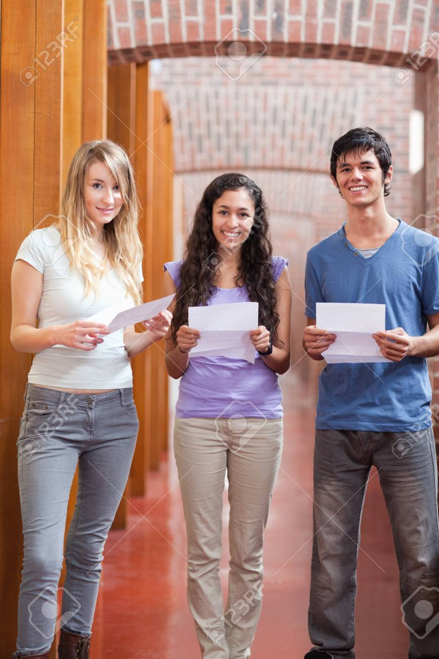 Portrait of smiling students holding a piece of paper in a corridor Stock Photo - 11181291