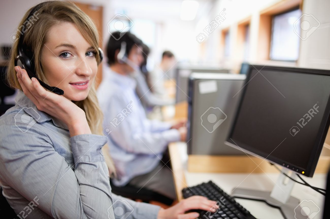 Smiling Blonde Operator Posing With A Headset In A Call Center ...