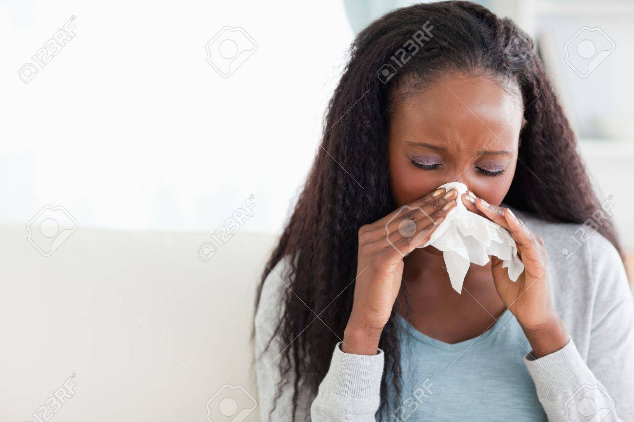 Close up of young woman blowing her nose on couch Stock Photo - 11619808