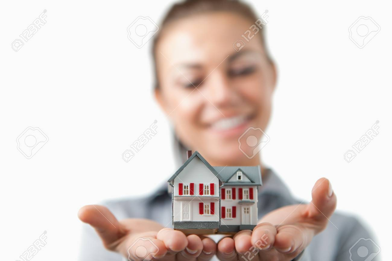 Close up of model house being held by female estate agent against a white background Stock Photo - 11624565