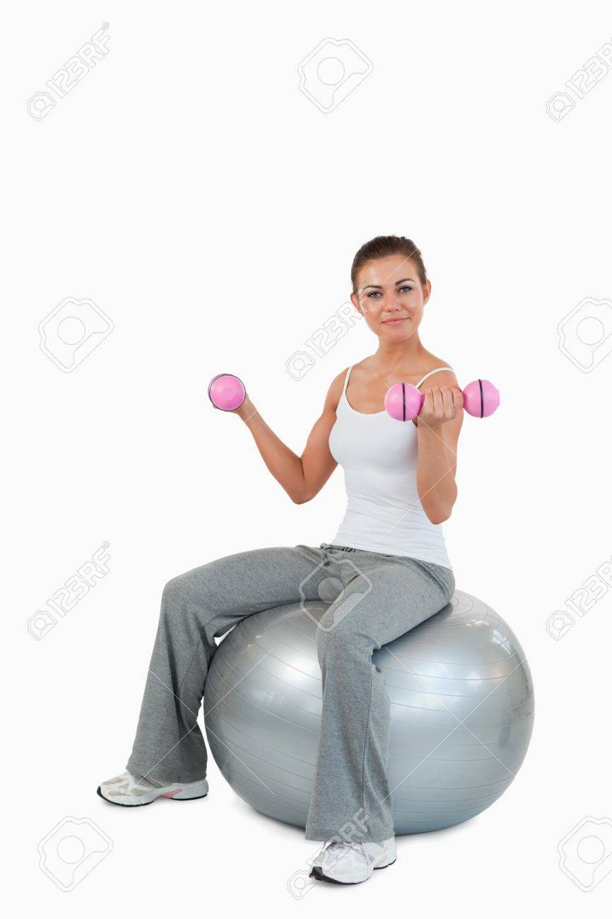 Portrait of a fit woman working out with dumbbells and a ball against a white background Stock Photo - 11624486