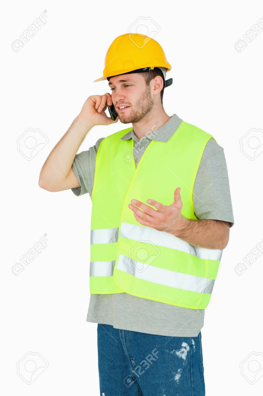 Young construction worker discussing on the cellphone against a white background Stock Photo - 11636583