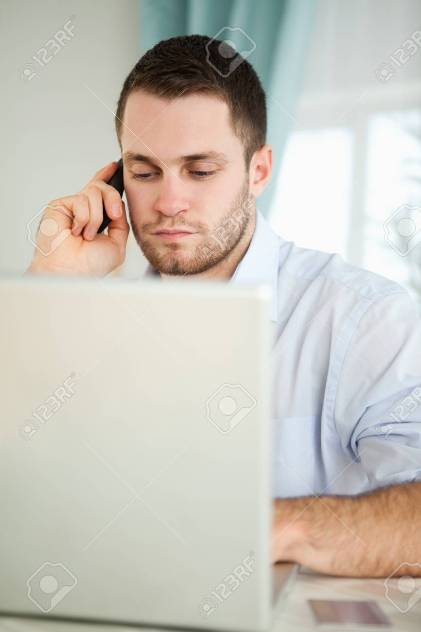 Young businessman in his homeoffice using his cellphone Stock Photo - 11634497