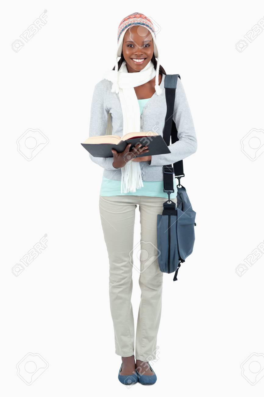 Smiling young female student having a look at her book against a white background Stock Photo - 11624710