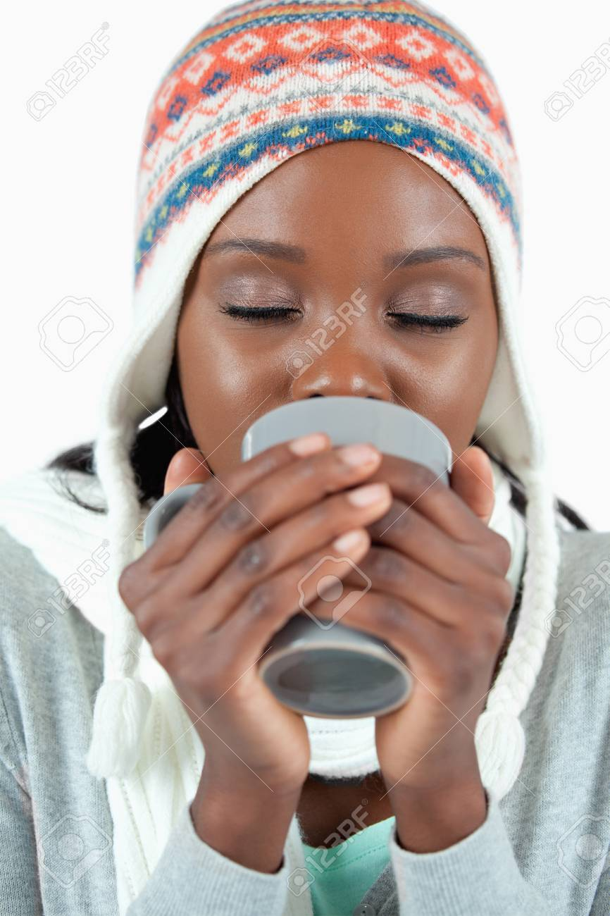 Young woman warming up with a cup of tea against a white background Stock Photo - 11632284
