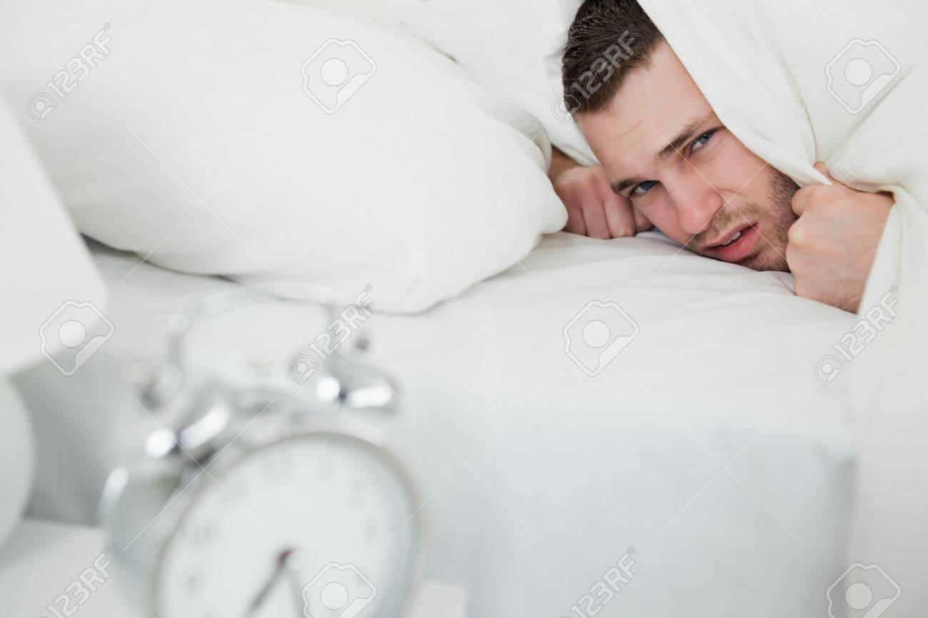 Verärgert mann hält sich die ohren, während sein wecker klingelt ...