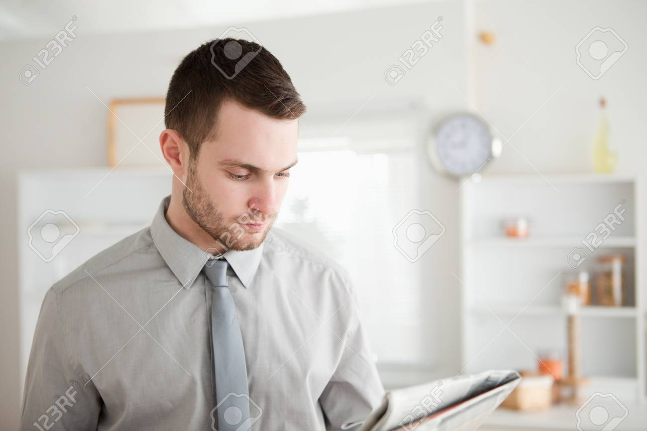 Businessman reading a newspaper in his kitchen Stock Photo - 11632590