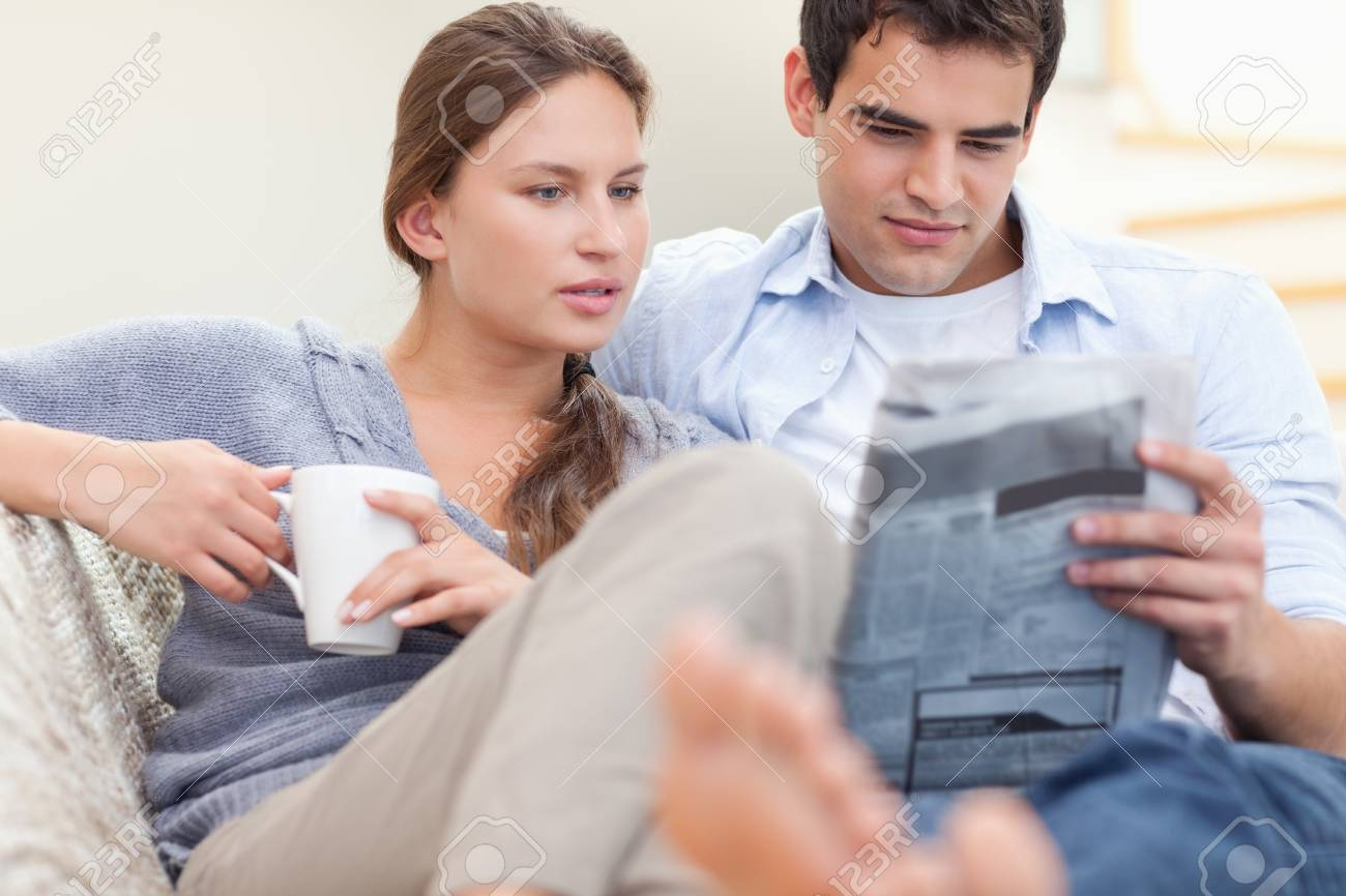 Couple reading the news while lying on a sofa Stock Photo - 11632553
