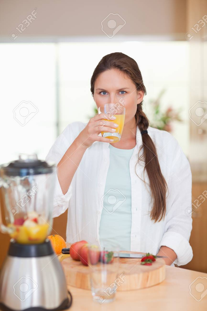 Portrait of a cute woman drinking fresh fruits juice in her kitchen Stock Photo - 11632235