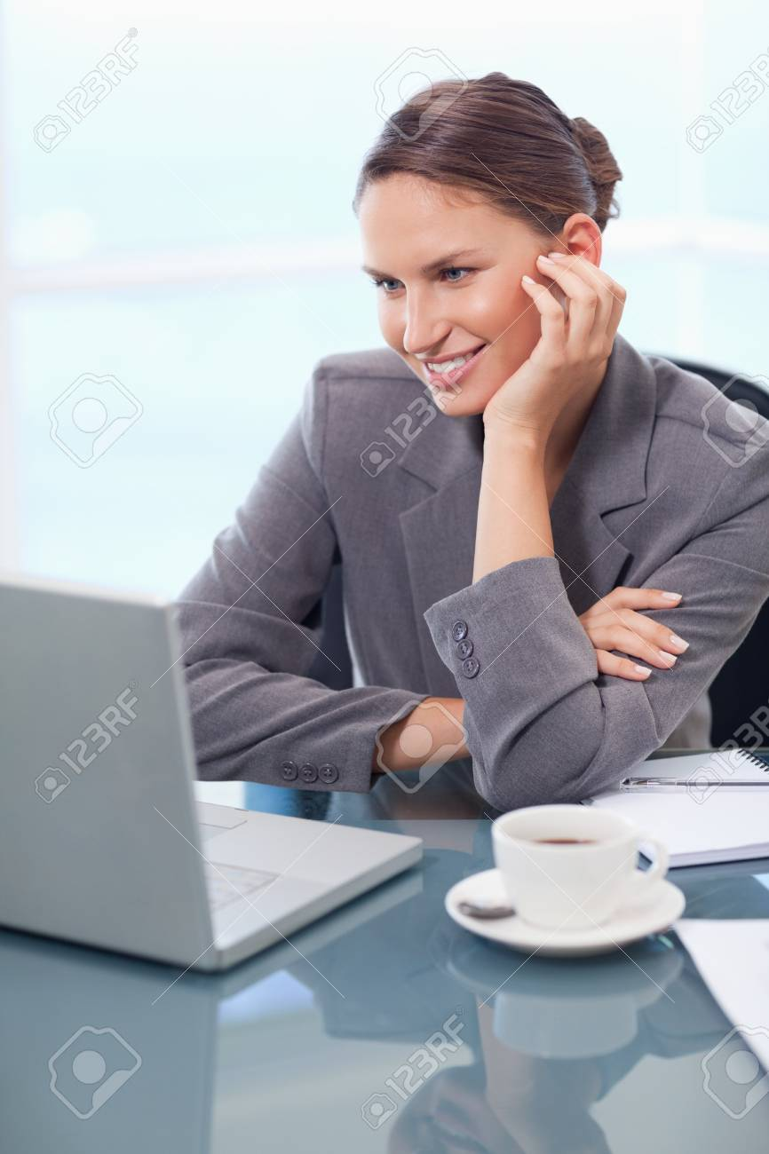 Portrait of a happy businesswoman working with a notebook in her office Stock Photo - 11632612