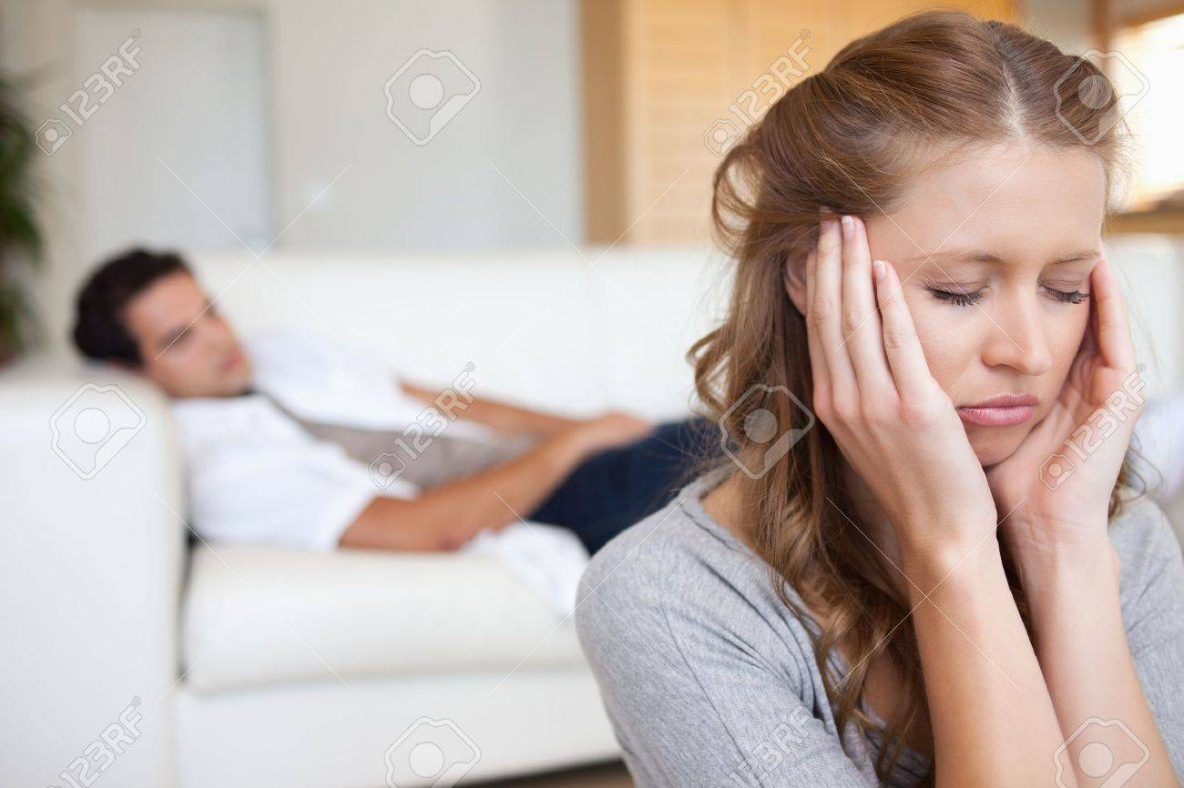 Young woman experiencing headache with man on the sofa behind her Stock Photo - 11716530