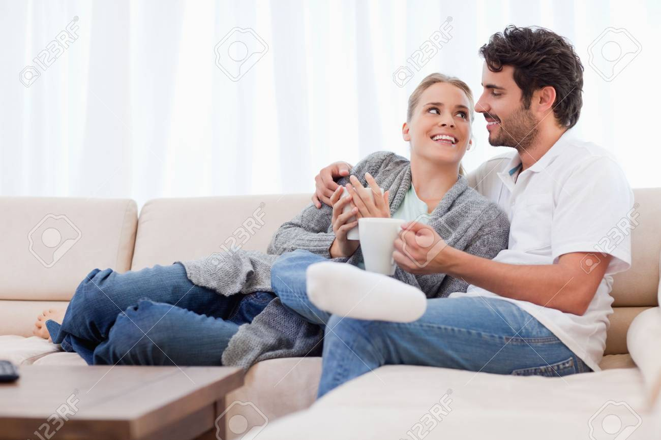 Young couple having a cup of coffee in their living room Stock Photo - 11684844