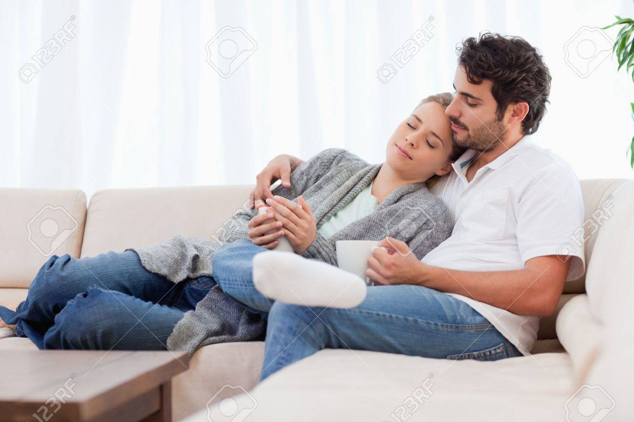 Lovely couple having a cup of tea in their living room Stock Photo - 11684936
