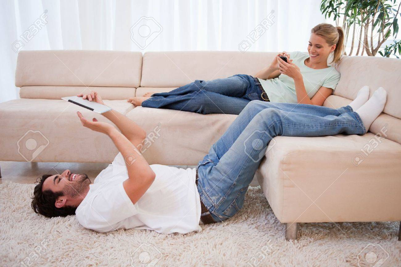 Woman using her smartphone while her boyfriend is using a tablet computer in their living room Stock Photo - 11681241