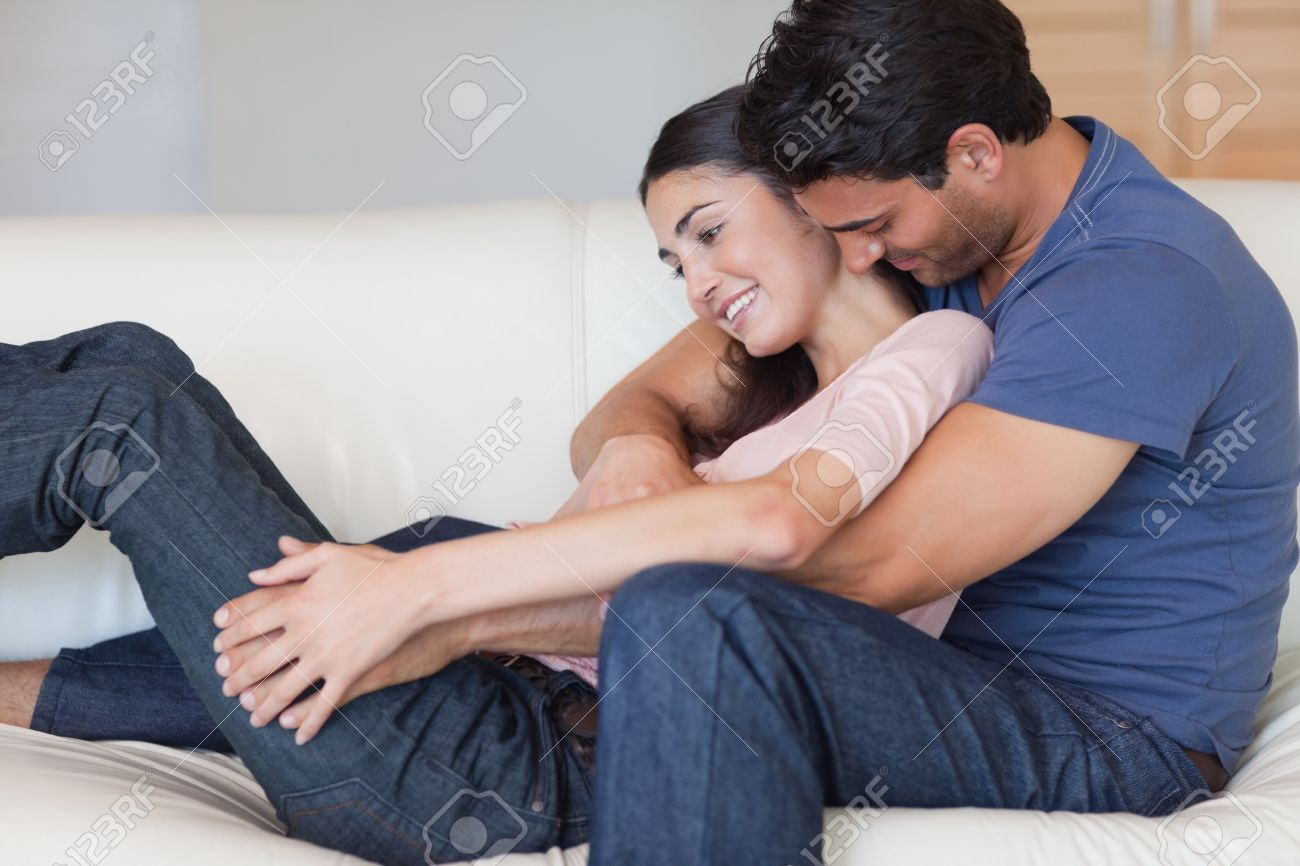 Man kissing his girlfriend in the neck in their living room Stock Photo - 11681496