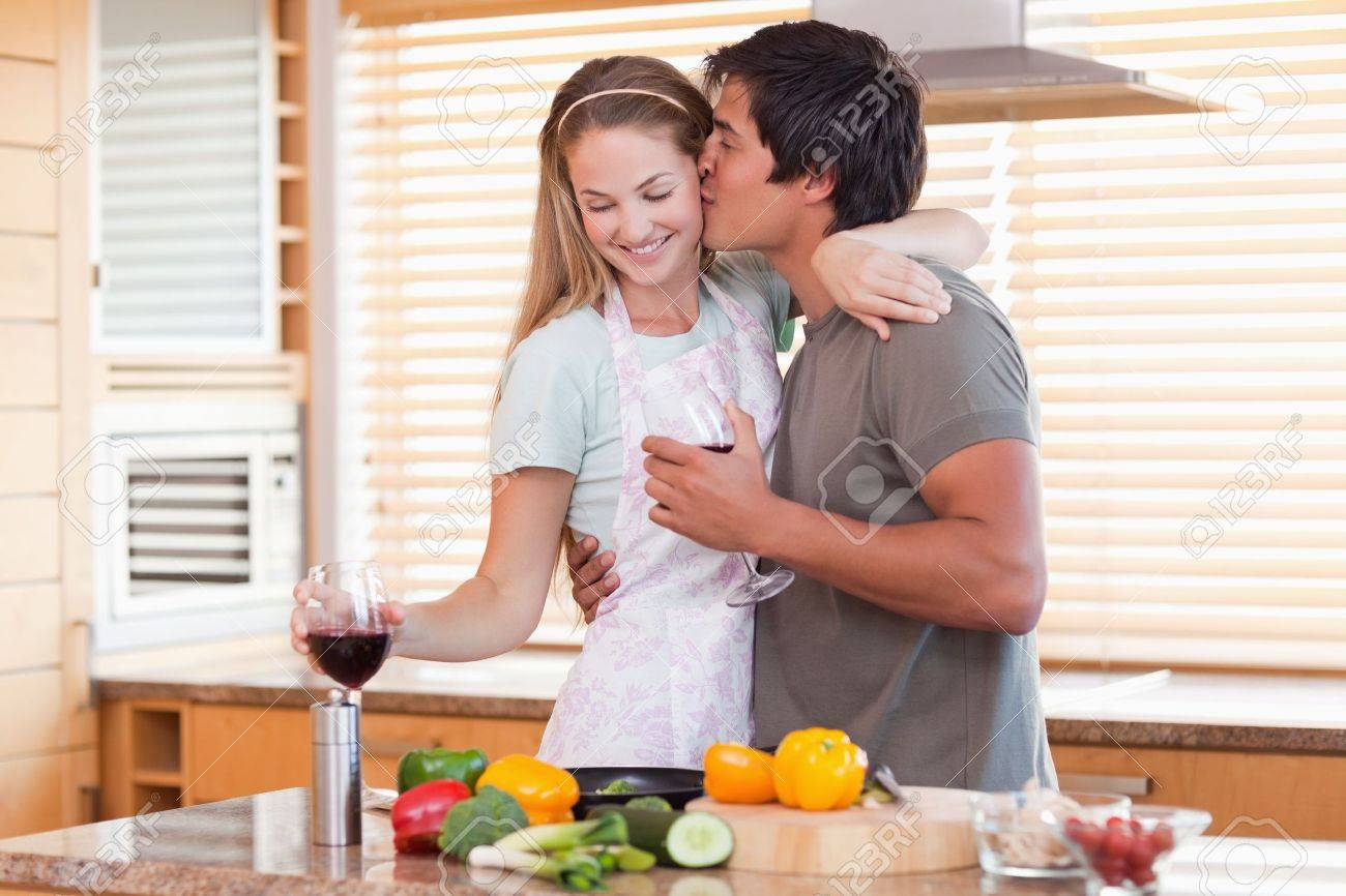 Lovely couple drinking red wine while kissing in their kitchen Stock Photo - 11683994