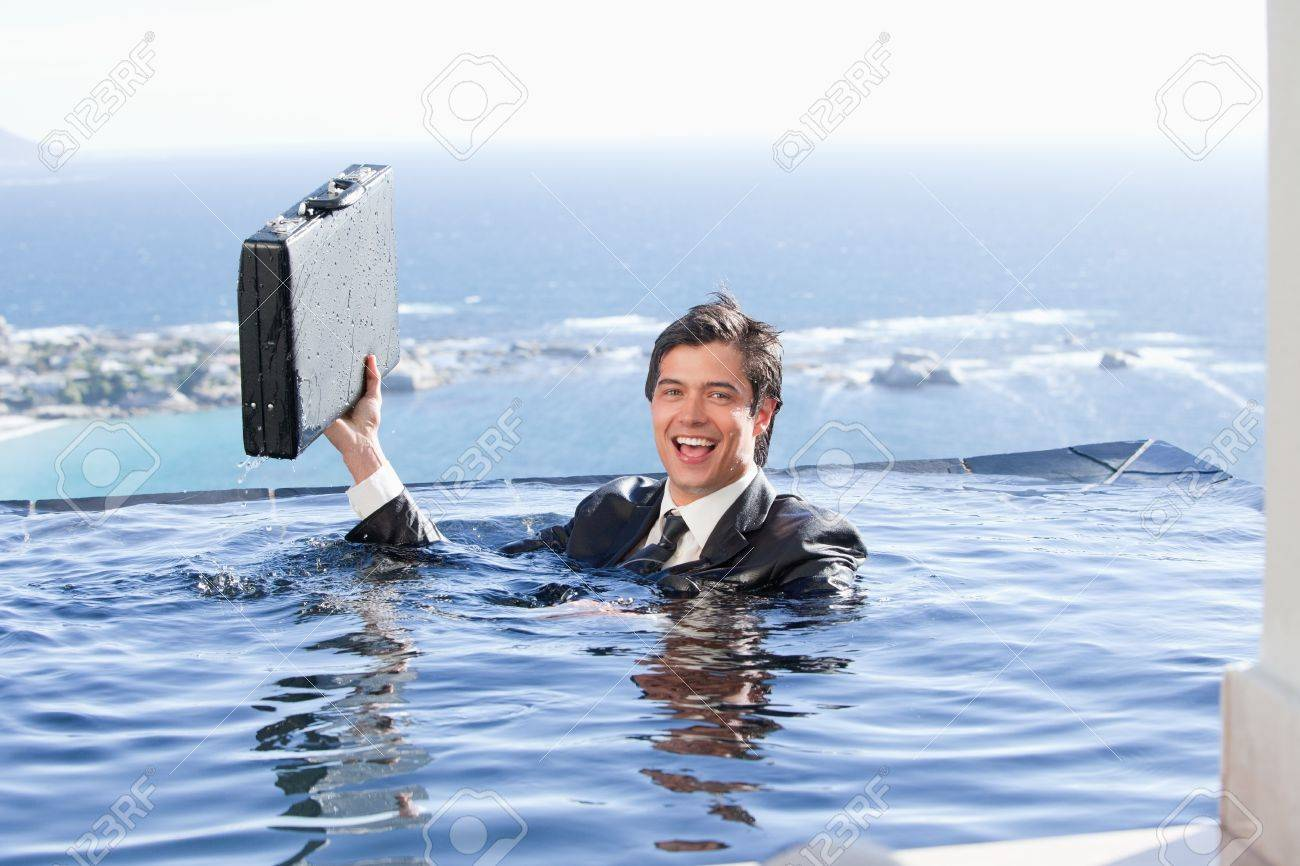 Businessman holding a briefcase in a swimming pool Stock Photo - 11683086