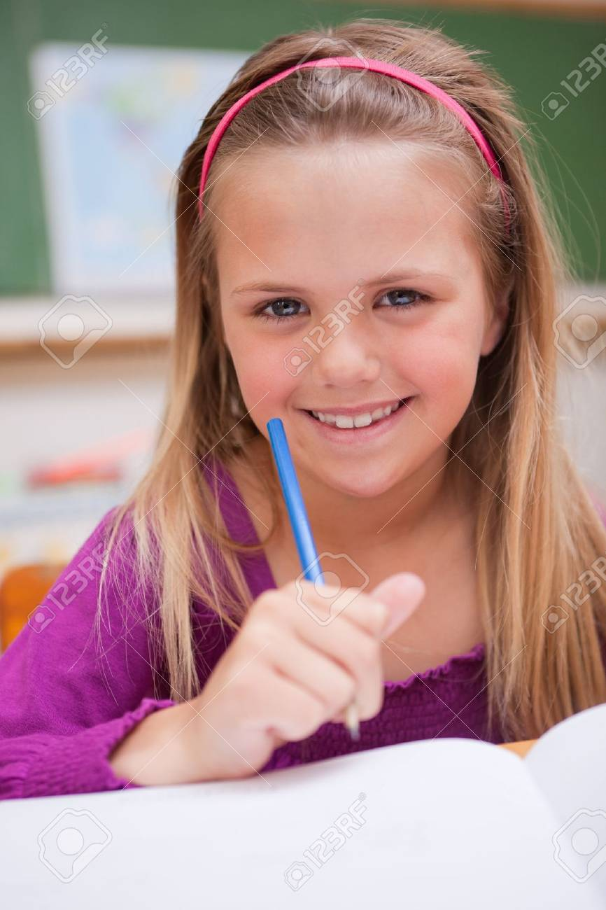 Portrait of a little schoolgirl writing on a book in a classroom Stock Photo - 11682342