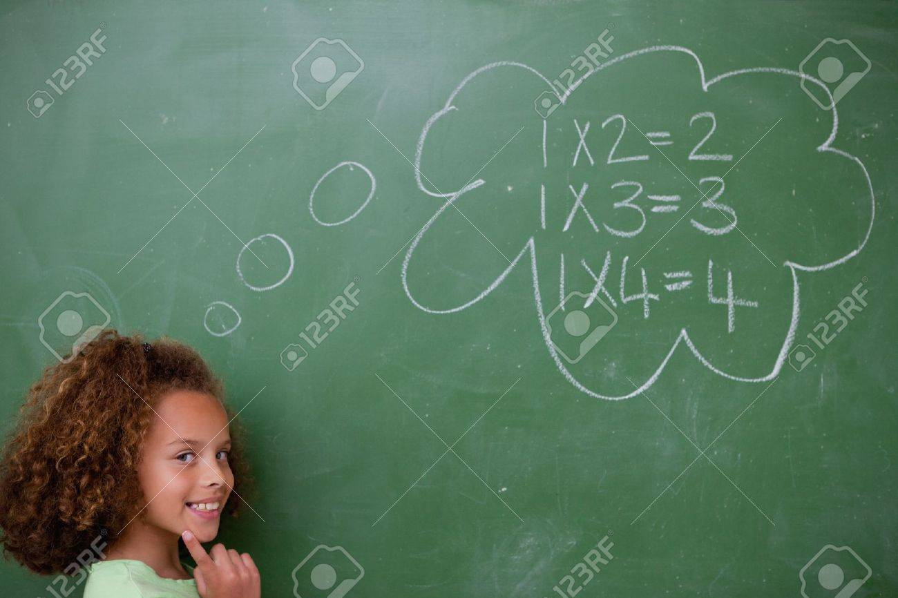 Schoolgirl thinking about mathematics in front of a blackboard Stock Photo - 11679589