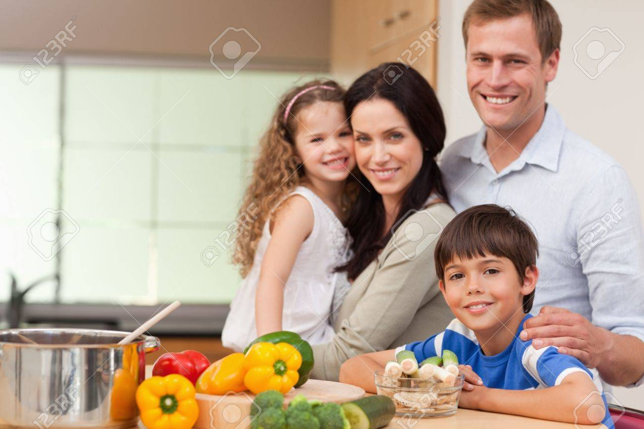 Smiling family standing in the kitchen together Stock Photo - 11684043