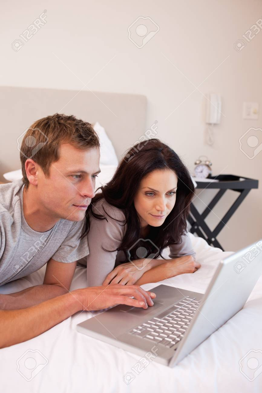 Young couple using laptop in the bedroom together Stock Photo - 11684565