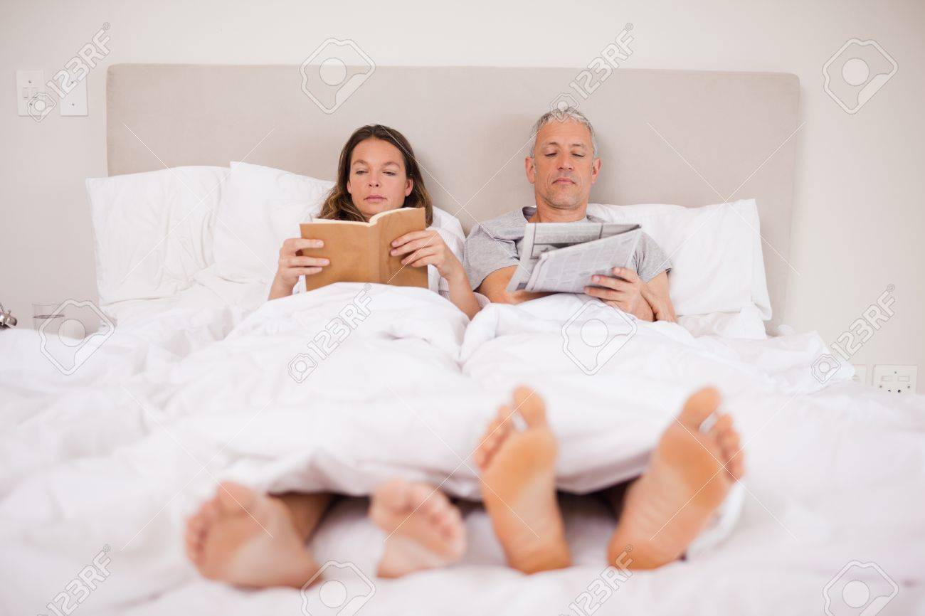 Man reading the news while his wife is reading a book in their bedroom Stock Photo - 11686301