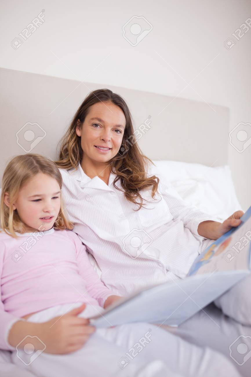 Portrait of a girl reading a book with her mother in a bedroom Stock Photo - 11685356
