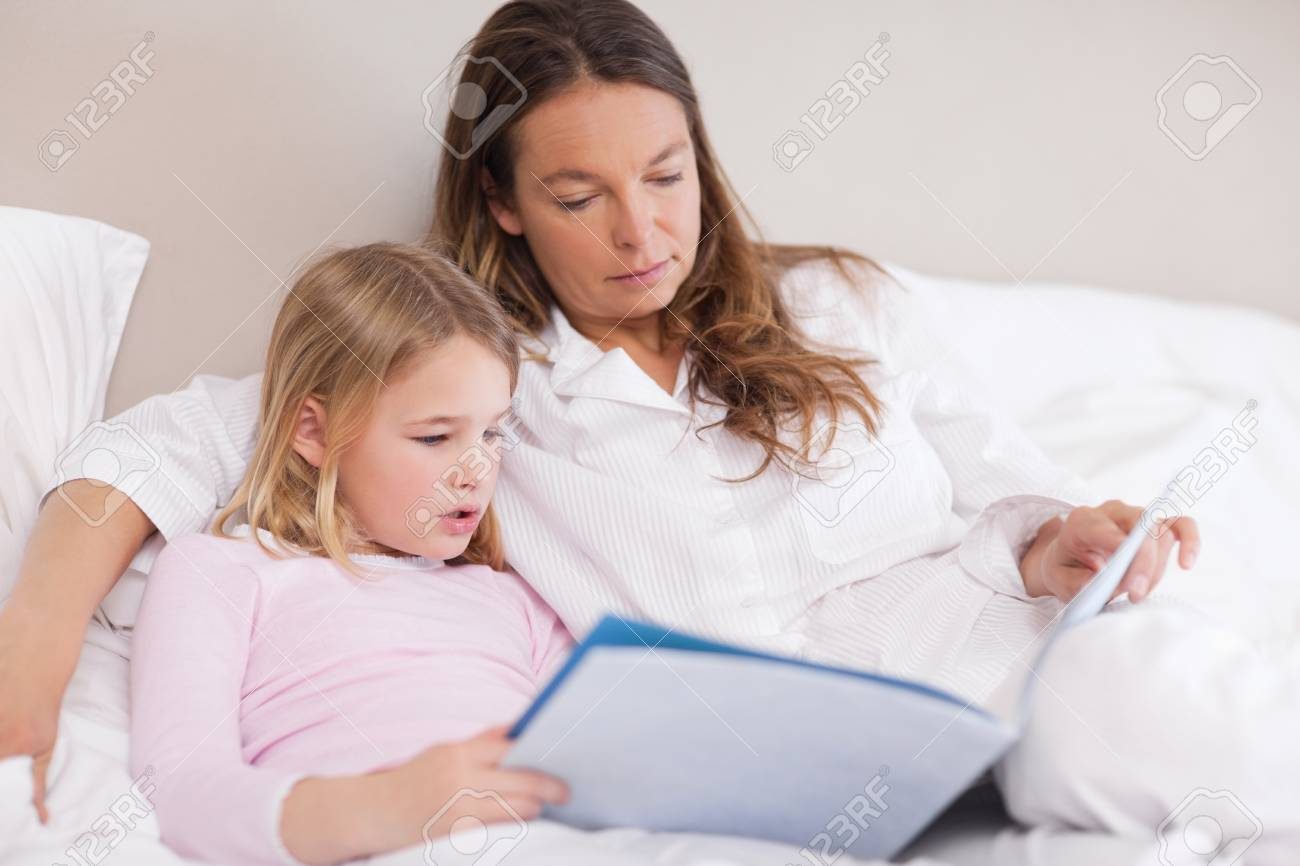 Cute girl reading a book with her mother in a bedroom Stock Photo - 11685443