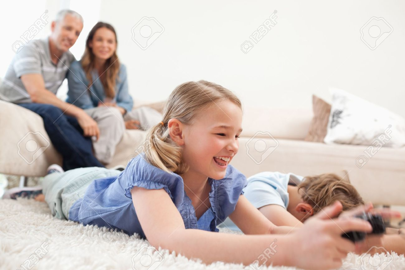 Children Playing Video Games With Their Parents On The Background In A Living Room Stock Photo