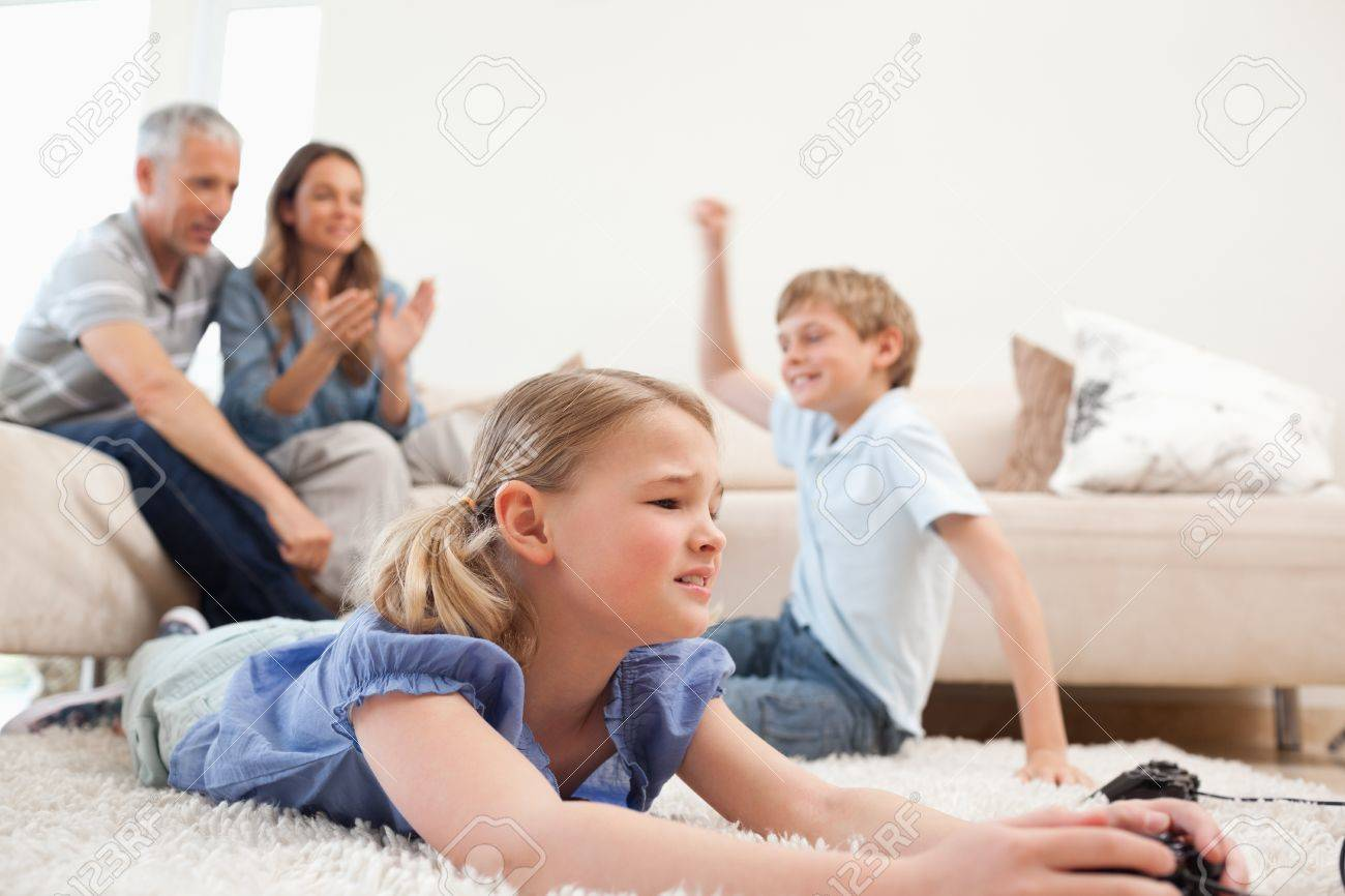 Cute Children Playing Video Games With Their Parents On The Background In Living Room Stock