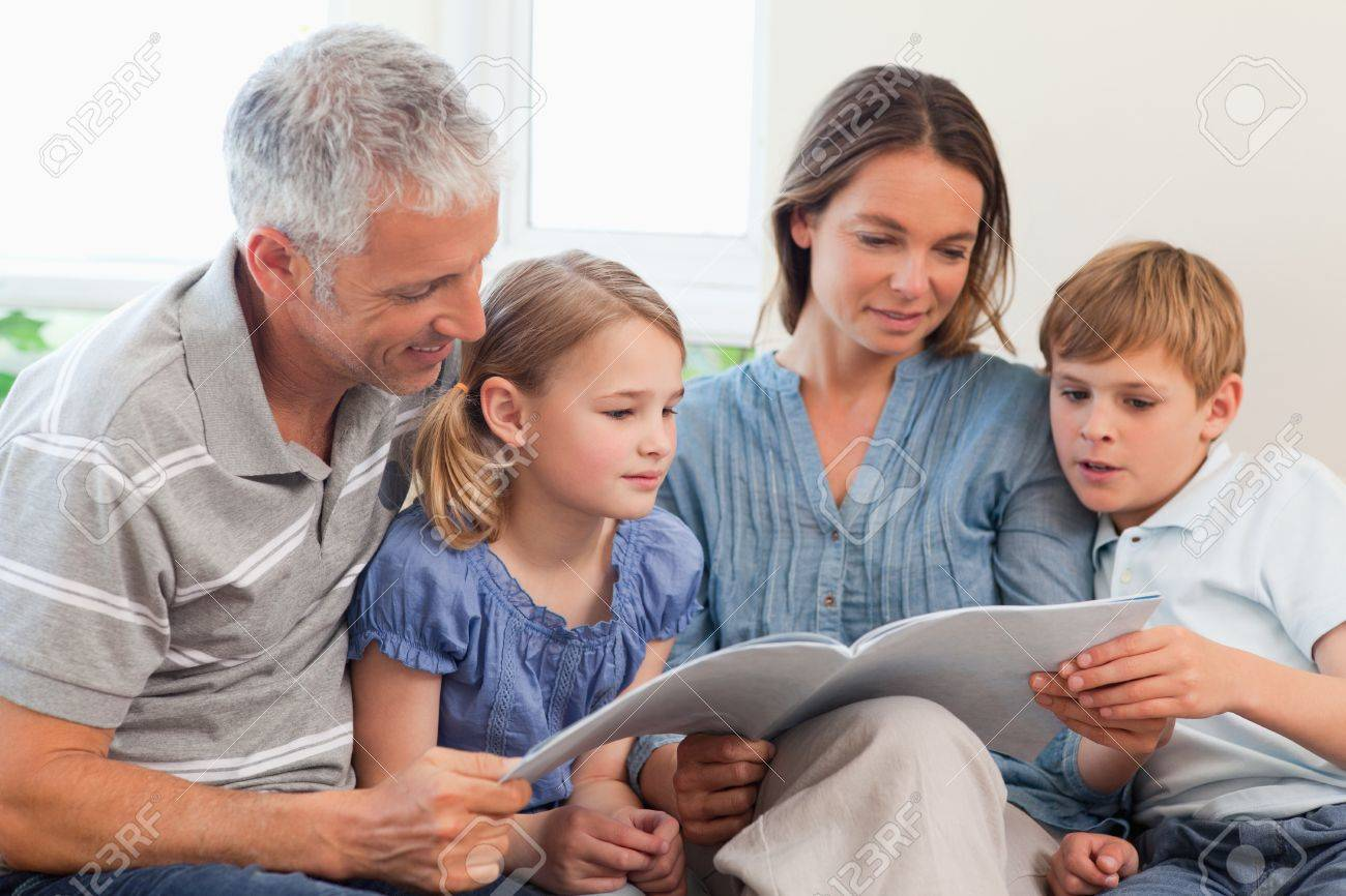 Family reading a book together in a living room Stock Photo - 11682793