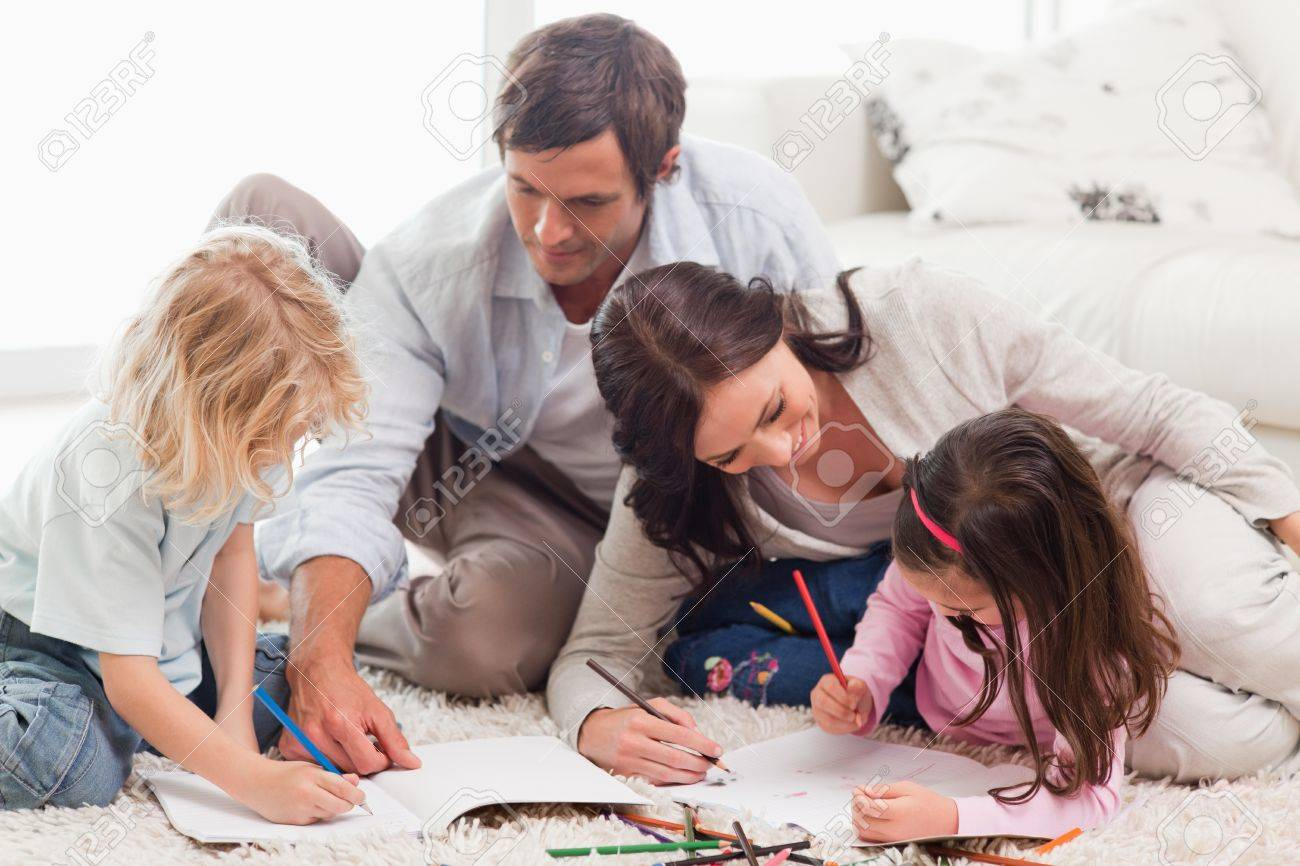 Beautiful family drawing together in a living room Stock Photo - 11683721