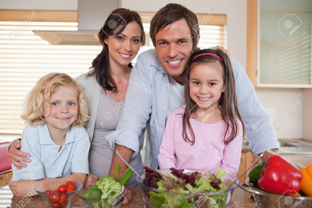 Family preparing a salad in a kitchen Stock Photo - 11681488
