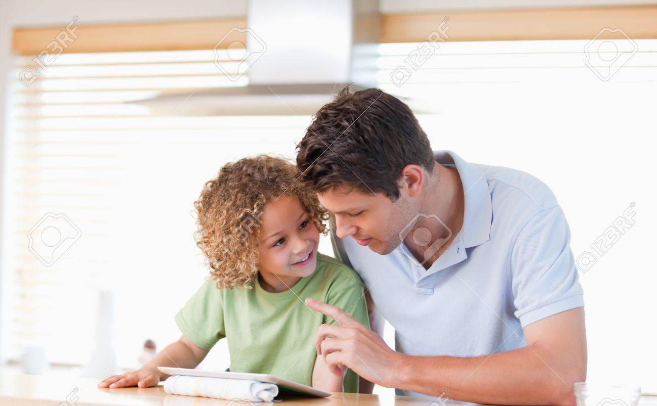 Young boy and his father using a tablet computer in their kitchen Stock Photo - 11686551