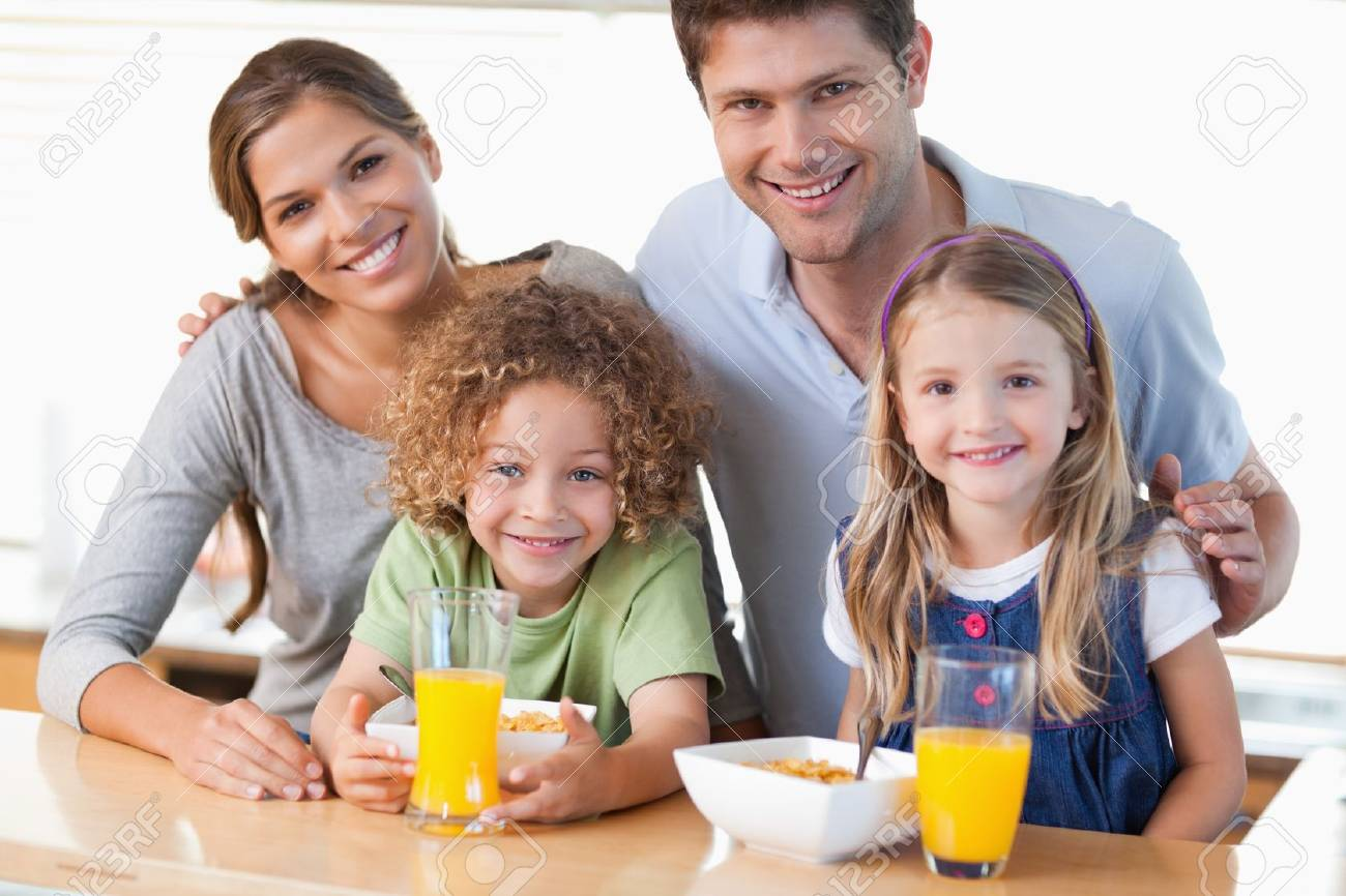Happy family in kitchen - Happy Family Having Breakfast In Their Kitchen Stock Photo 11684346