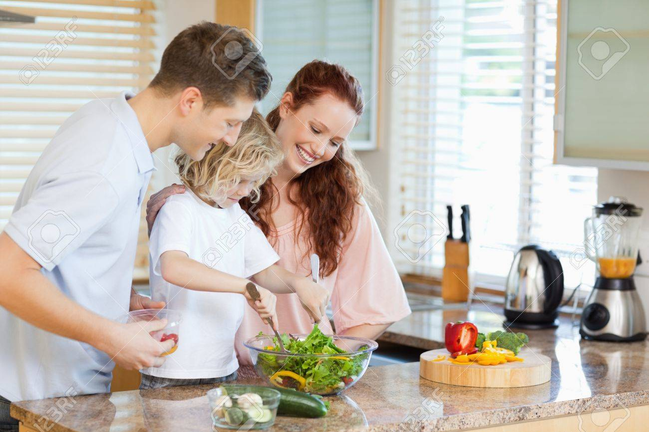 Couple letting their young child stir the salad Stock Photo - 11682943
