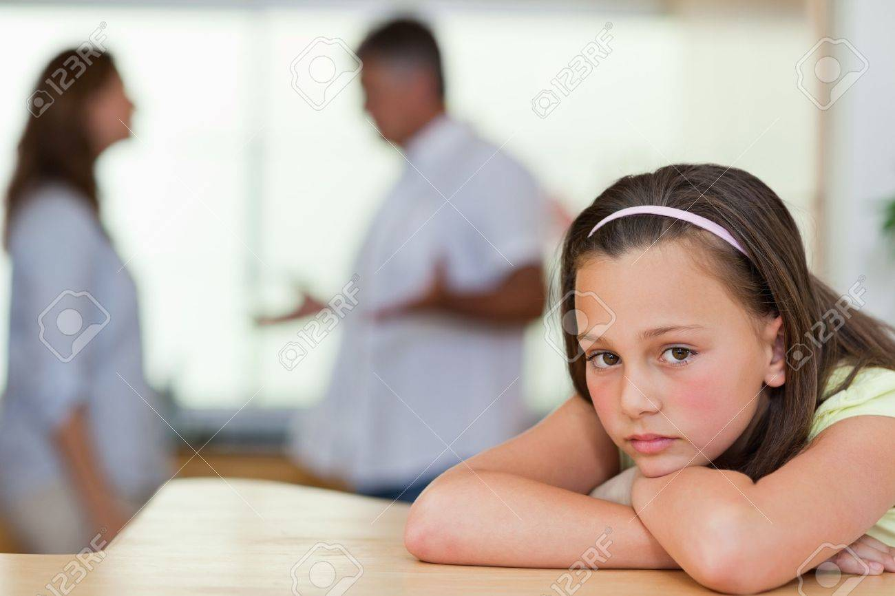 Sad girl with her fighting parents behind her Stock Photo - 11685171