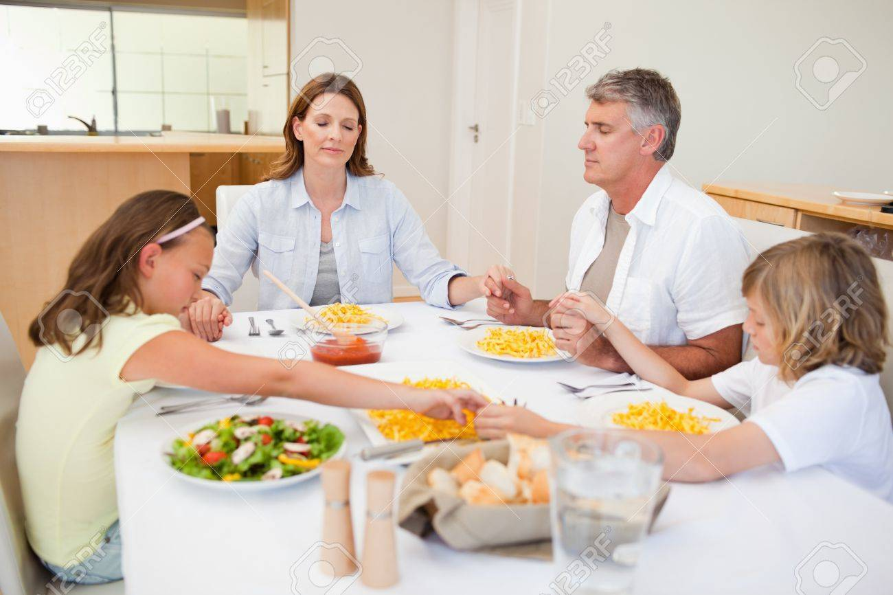 Family saying grace together Stock Photo - 11685579