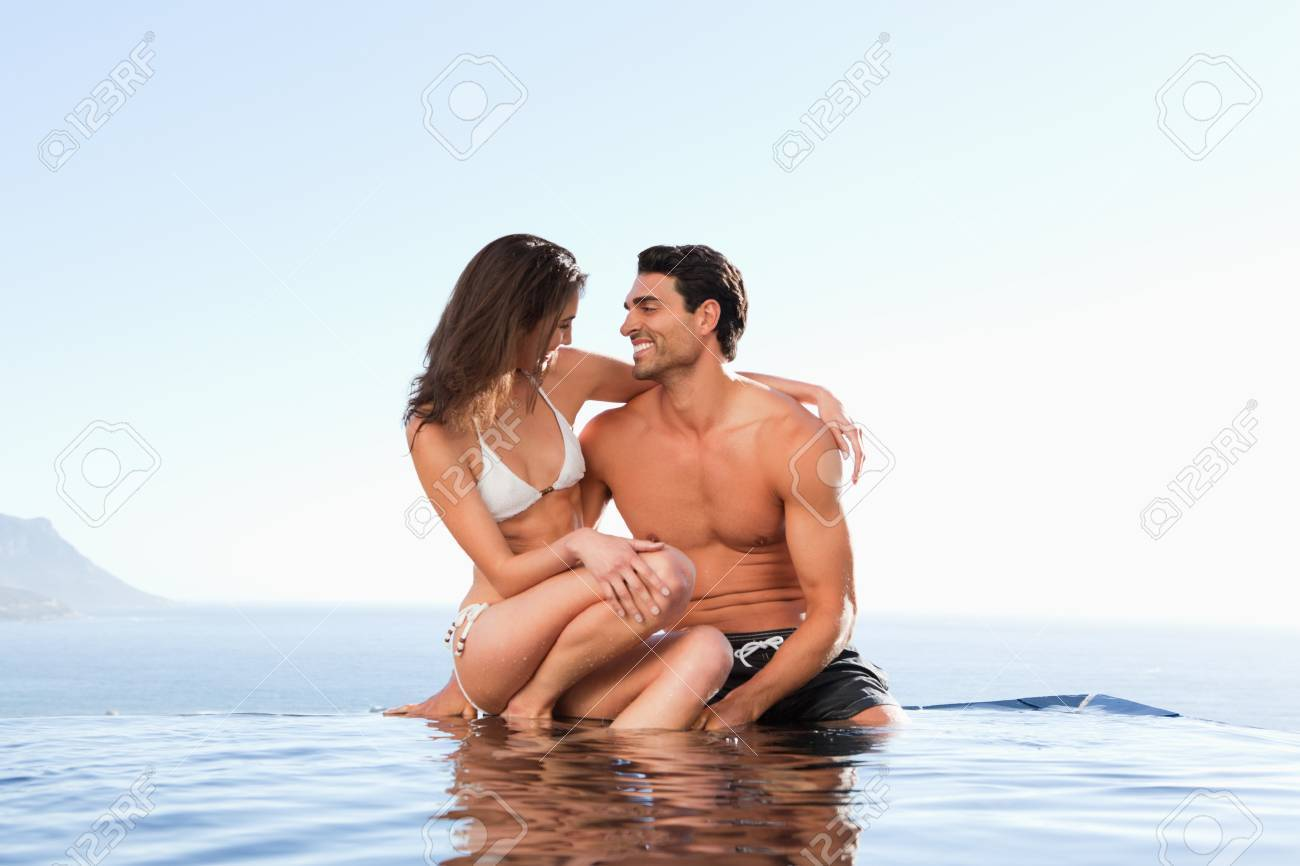 Couple sitting on the pool edge together Stock Photo - 11686999