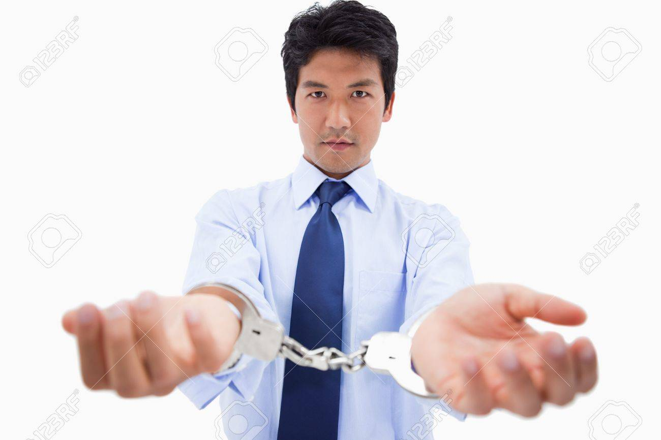 Businessman with handcuffs against a white background Stock Photo - 11687089