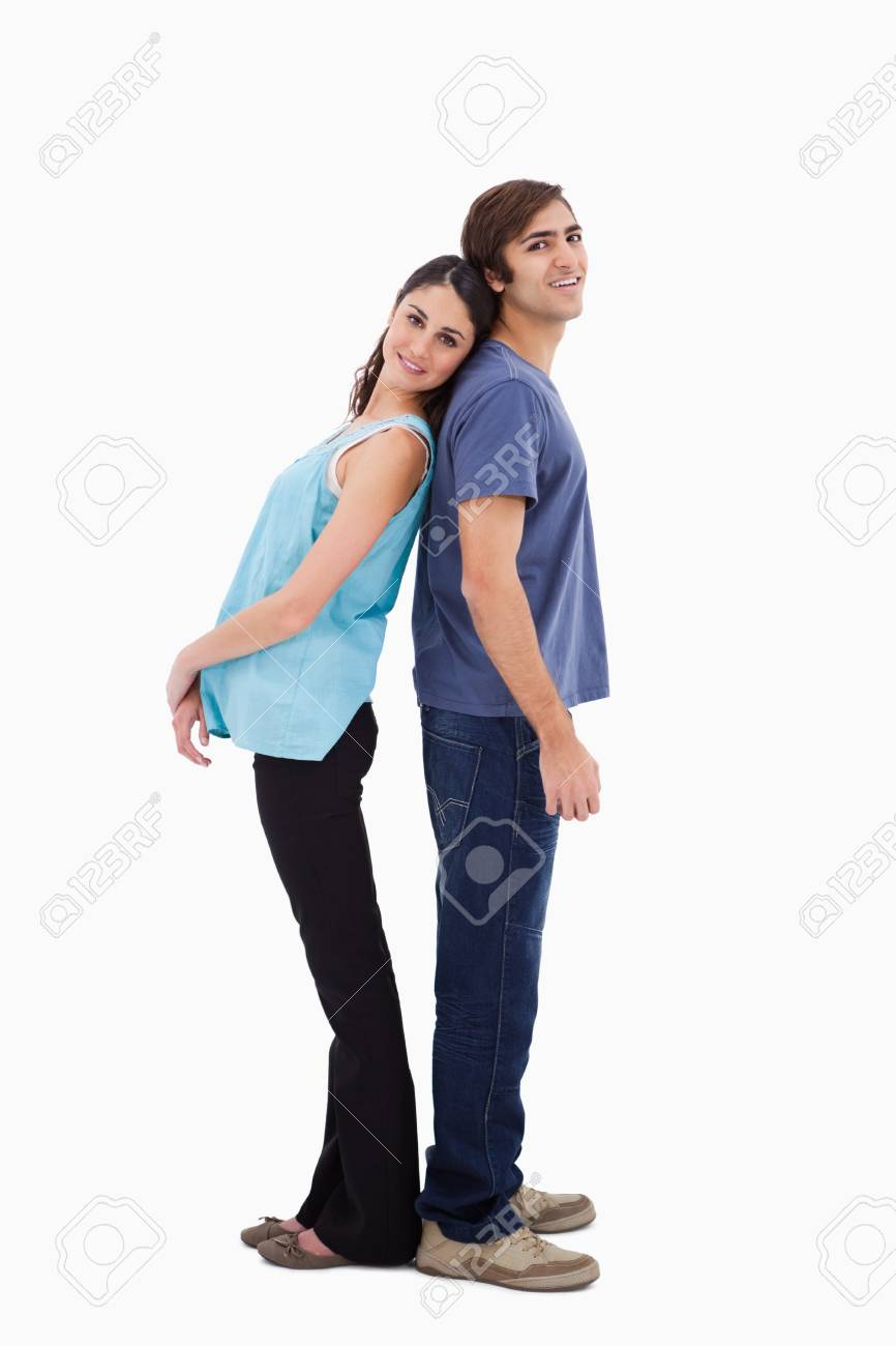 Portrait of a young couple standing back to back against a white background Stock Photo - 11687386