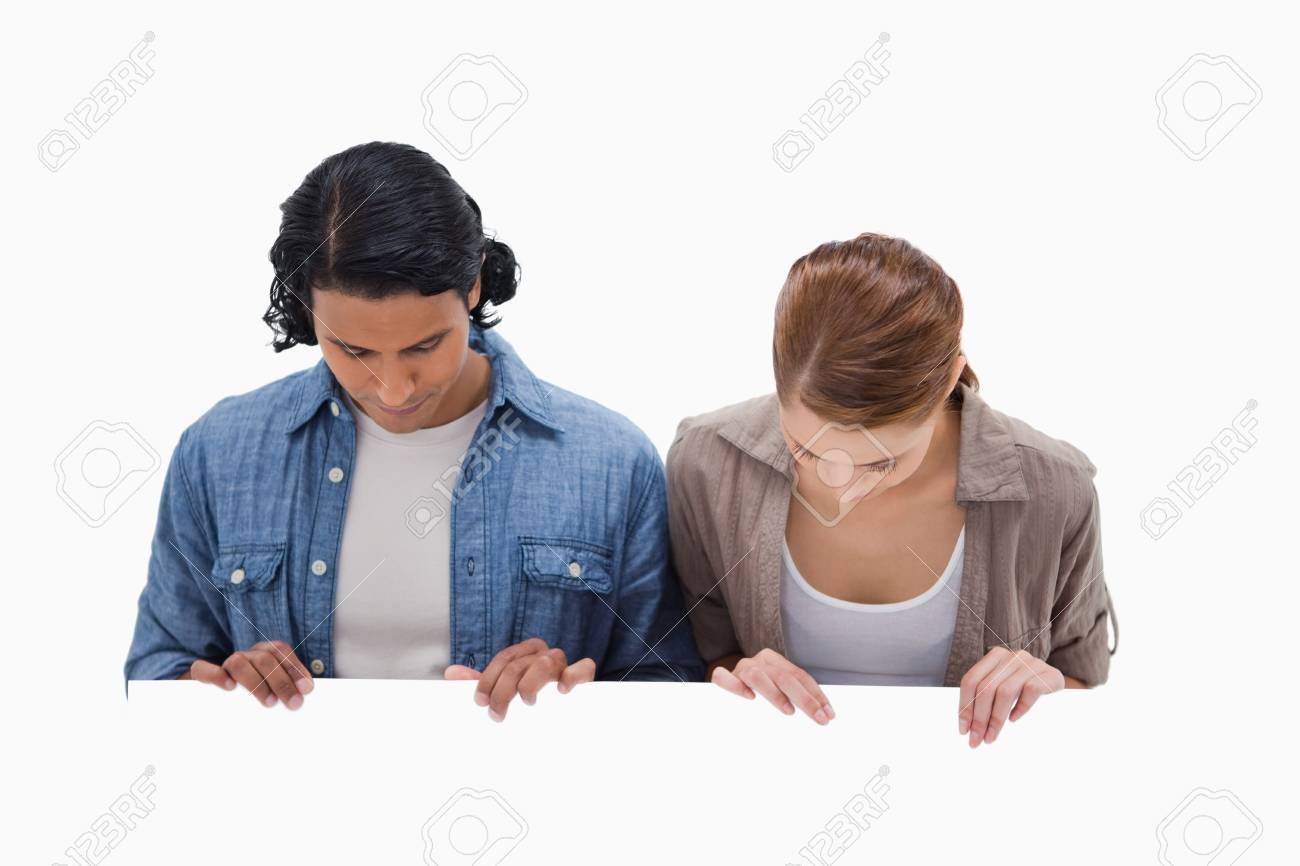 Couple looking down on blank wall against a white background Stock Photo - 11687050