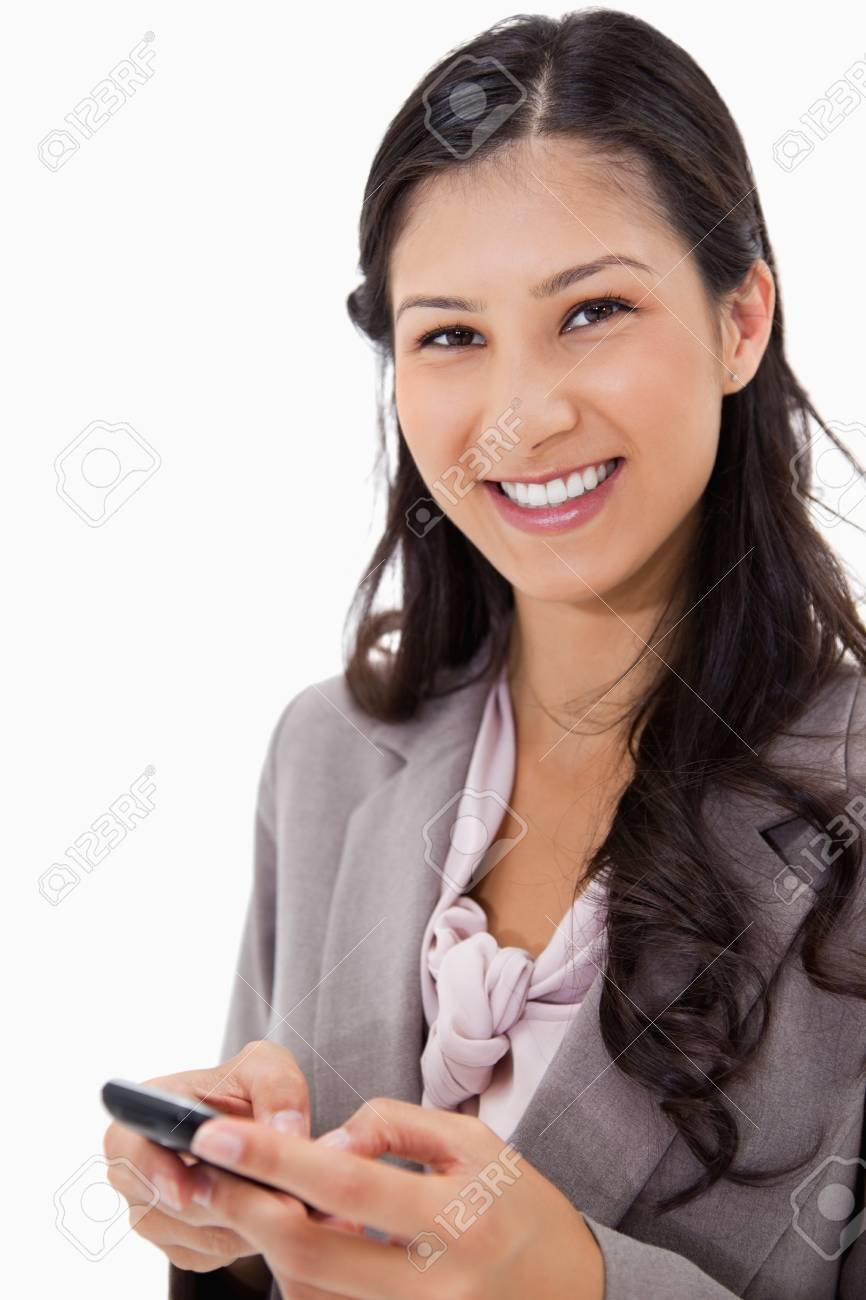 Smiling woman holding cellphone against a white background Stock Photo - 11685564
