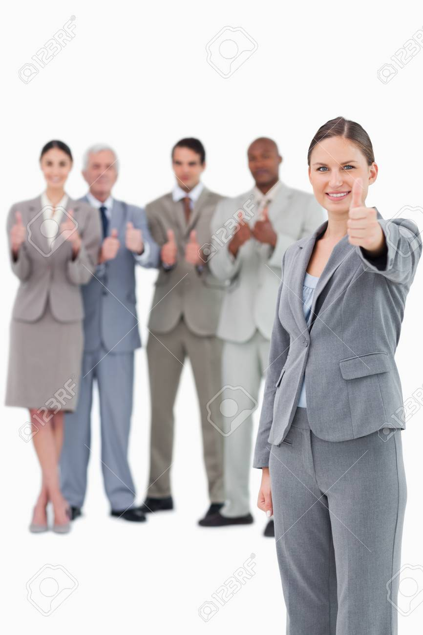 Saleswoman with thumb up and her team behind her against a white background Stock Photo - 13615106
